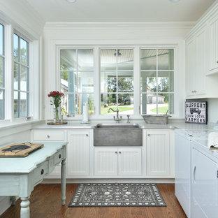 Foto på ett lantligt grå grovkök, med en rustik diskho, luckor med infälld panel, vita skåp, vita väggar, mörkt trägolv, en tvättmaskin och torktumlare bredvid varandra, brunt golv och laminatbänkskiva