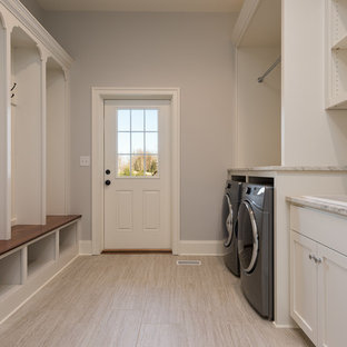 This is an example of a large transitional galley utility room in Other with a drop-in sink, shaker cabinets, white cabinets, limestone benchtops, grey walls, porcelain floors, a side-by-side washer and dryer and beige floor.