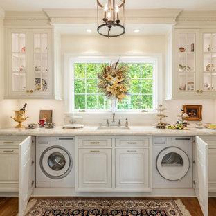 Inspiration för ett mellanstort vintage vit linjärt vitt grovkök, med en undermonterad diskho, luckor med upphöjd panel, vita skåp, bänkskiva i kvartsit, vitt stänkskydd, vita väggar, mellanmörkt trägolv, tvättmaskin och torktumlare byggt in i ett skåp och brunt golv