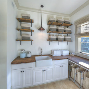 Laundry room - coastal laundry room idea in Jacksonville with a farmhouse sink, white walls, wood countertops and brown countertops