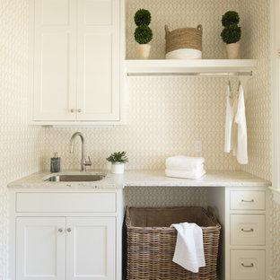 Esempio di una sala lavanderia costiera con lavello sottopiano, ante in stile shaker, ante bianche, pavimento beige e pareti beige