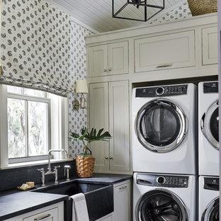 Immagine di una sala lavanderia stile marinaro con lavello stile country, ante in stile shaker, ante grigie, pareti multicolore, pavimento nero e top nero