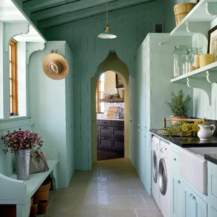 Laundry room - mediterranean gray floor laundry room idea in Austin with a farmhouse sink and black countertops