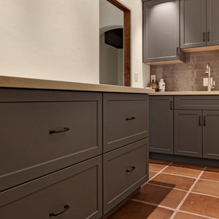 Dedicated laundry room - mid-sized southwestern l-shaped terra-cotta tile and brown floor dedicated laundry room idea in Phoenix with an undermount sink, shaker cabinets, gray cabinets, white walls, a side-by-side washer/dryer and white countertops