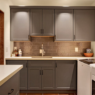 Mid-sized southwest l-shaped terra-cotta tile and brown floor dedicated laundry room photo in Phoenix with an undermount sink, shaker cabinets, gray cabinets, white walls, a side-by-side washer/dryer and white countertops