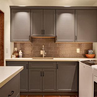 Immagine di una sala lavanderia stile americano di medie dimensioni con lavello sottopiano, ante in stile shaker, ante grigie, pareti bianche, pavimento in terracotta, lavatrice e asciugatrice affiancate, pavimento marrone e top bianco