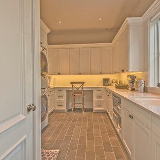 Idéer för mycket stora lantliga u-formade beige tvättstugor enbart för tvätt, med en undermonterad diskho, vita skåp, bänkskiva i kvarts, vita väggar, skiffergolv, en tvättpelare, skåp i shakerstil och brunt golv