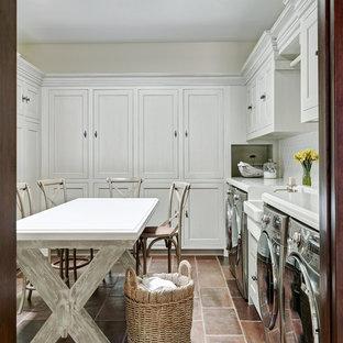 Foto di una grande lavanderia multiuso mediterranea con lavello stile country, ante in stile shaker, ante bianche, pareti beige, lavatrice e asciugatrice affiancate e top bianco