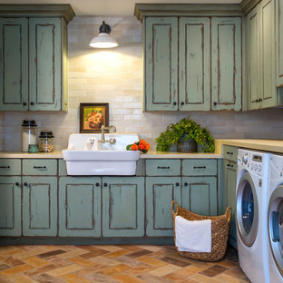 This is an example of a large mediterranean separated utility room in Phoenix with a belfast sink, raised-panel cabinets, green cabinets, concrete worktops, white walls, terracotta flooring, a side by side washer and dryer and multi-coloured floors.