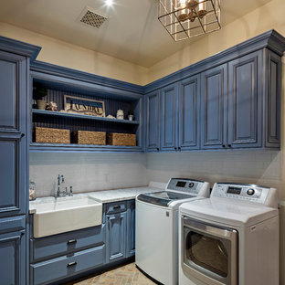 Mid-sized tuscan l-shaped brick floor dedicated laundry room photo in Phoenix with a farmhouse sink, raised-panel cabinets, blue cabinets, quartzite countertops and beige walls