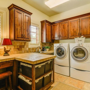 Example of a large tuscan l-shaped ceramic tile and beige floor dedicated laundry room design in Austin with an utility sink, raised-panel cabinets, medium tone wood cabinets, tile countertops, beige walls, a side-by-side washer/dryer and beige countertops