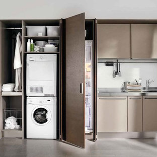 Small modern single-wall utility room in New York with a drop-in sink, flat-panel cabinets, stainless steel benchtops, white walls, concrete floors, a stacked washer and dryer, grey floor and brown cabinets.