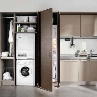 Idéer för små funkis linjära grovkök, med en nedsänkt diskho, släta luckor, bänkskiva i rostfritt stål, vita väggar, betonggolv, en tvättpelare, grått golv och bruna skåp