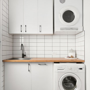 Inspiration for a contemporary single-wall separated utility room in Melbourne with a built-in sink, flat-panel cabinets, white cabinets, wood worktops, white walls, black floors and brown worktops.