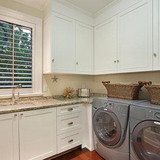 Ispirazione per una grande sala lavanderia tropicale con lavello a vasca singola, ante in stile shaker, ante bianche, top in granito, pareti beige, pavimento in legno massello medio e lavatrice e asciugatrice affiancate