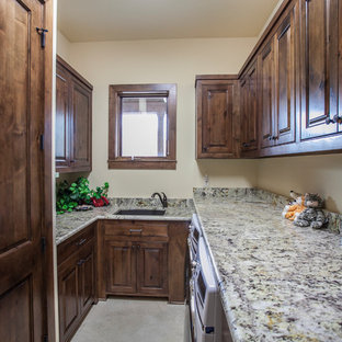 Small mountain style galley beige floor dedicated laundry room photo in Austin with an undermount sink, raised-panel cabinets, dark wood cabinets, granite countertops and beige walls