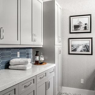Foto di una sala lavanderia stile marino di medie dimensioni con lavello sottopiano, ante in stile shaker, ante grigie, top in quarzo composito, pareti grigie, pavimento in gres porcellanato, lavatrice e asciugatrice affiancate, pavimento grigio e top bianco