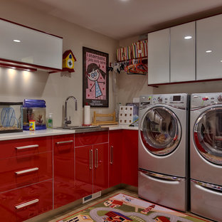 Inspiration for a contemporary l-shaped laundry room remodel in Omaha with a drop-in sink, flat-panel cabinets, red cabinets, beige walls and a side-by-side washer/dryer