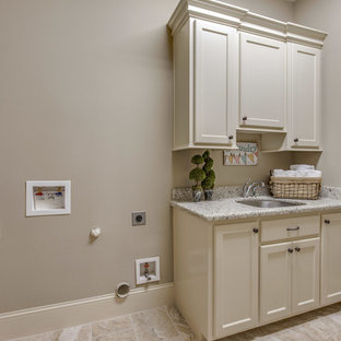 Large mediterranean single-wall separated utility room in Houston with a submerged sink, recessed-panel cabinets, white cabinets, granite worktops, beige walls, ceramic flooring, a side by side washer and dryer and beige floors.