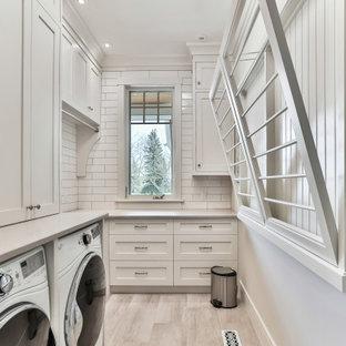 Exempel på en maritim grå l-formad grått tvättstuga enbart för tvätt, med skåp i shakerstil, vita skåp, vita väggar, en tvättmaskin och torktumlare bredvid varandra och beiget golv
