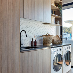 Immagine di una sala lavanderia minimal con lavello sottopiano, ante lisce, ante in legno scuro, pareti bianche, lavatrice e asciugatrice affiancate, pavimento grigio e top nero