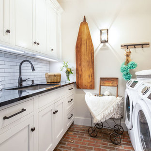 Lantlig inredning av en svarta svart tvättstuga enbart för tvätt, med en undermonterad diskho, skåp i shakerstil, vita skåp, vita väggar, tegelgolv, en tvättmaskin och torktumlare bredvid varandra och rött golv