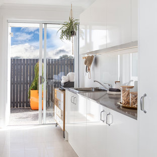 Midcentury galley dedicated laundry room in Canberra - Queanbeyan with a drop-in sink, white cabinets, granite benchtops, white walls, ceramic floors, grey benchtop, flat-panel cabinets and white floor.