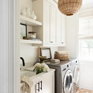 Idéer för en liten klassisk vita linjär tvättstuga enbart för tvätt, med en undermonterad diskho, skåp i shakerstil, vita skåp, vita väggar, klinkergolv i keramik, orange golv och en tvättmaskin och torktumlare bredvid varandra