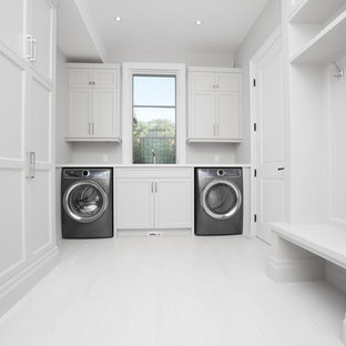 Inspiration for a large traditional u-shaped separated utility room in Toronto with a double-bowl sink, recessed-panel cabinets, white cabinets, engineered stone countertops, white walls, porcelain flooring and white floors.