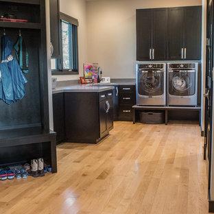 Cette image montre une buanderie minimaliste en U multi-usage et de taille moyenne avec un évier encastré, un placard à porte shaker, des portes de placard noires, un plan de travail en granite, un mur beige, un sol en bois clair, des machines côte à côte et un sol marron.