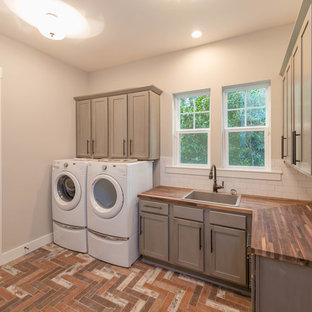 Ispirazione per una lavanderia stile marinaro di medie dimensioni con lavello da incasso, ante grigie, top in legno, pareti grigie, pavimento con piastrelle in ceramica, lavatrice e asciugatrice affiancate, top marrone e ante in stile shaker