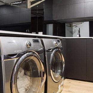 Ispirazione per una sala lavanderia minimalista di medie dimensioni con lavello da incasso, ante lisce, ante nere, pareti nere, pavimento in legno massello medio, lavatrice e asciugatrice affiancate, pavimento marrone e top bianco
