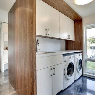 Esempio di una lavanderia minimalista con ante lisce, ante bianche, pareti bianche, lavatrice e asciugatrice affiancate, pavimento blu e top bianco