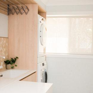 Идея дизайна: маленькая отдельная, линейная прачечная в скандинавском стиле с врезной раковиной, плоскими фасадами, светлыми деревянными фасадами, столешницей из кварцевого агломерата, полом из керамогранита, с сушильной машиной на стиральной машине, коричневым полом и белой столешницей