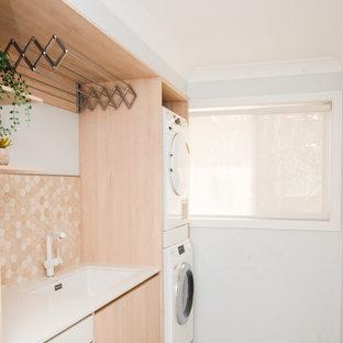 Ispirazione per una piccola sala lavanderia scandinava con lavello sottopiano, ante lisce, ante in legno chiaro, top in quarzo composito, pavimento in gres porcellanato, lavatrice e asciugatrice a colonna, pavimento marrone e top bianco