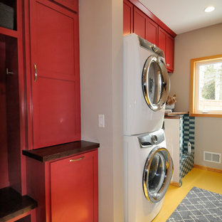 Mid-sized trendy single-wall laminate floor and yellow floor utility room photo in Minneapolis with an undermount sink, shaker cabinets, red cabinets, wood countertops, beige walls and a stacked washer/dryer