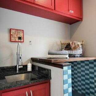 Modern inredning av ett mellanstort linjärt grovkök, med en undermonterad diskho, skåp i shakerstil, röda skåp, träbänkskiva, beige väggar, laminatgolv, en tvättpelare och gult golv