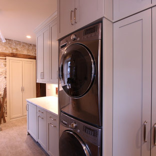 Stacked Washer and Dryer Next to Folding Counter with Marble Countertop