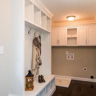 Klassisk inredning av ett l-format grovkök, med skåp i shakerstil, vita skåp, beige väggar, mörkt trägolv och brunt golv