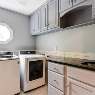 Photo of a medium sized traditional l-shaped utility room in Louisville with a submerged sink, raised-panel cabinets, grey cabinets, granite worktops, grey walls, marble flooring, a side by side washer and dryer, white floors and black worktops.