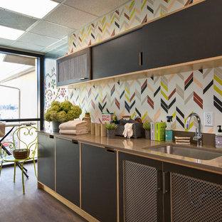 Idée de décoration pour une grande buanderie parallèle minimaliste multi-usage avec un évier encastré, un placard avec porte à panneau encastré, des portes de placard en bois clair, un plan de travail en surface solide, un mur multicolore, un sol en vinyl et des machines superposées.