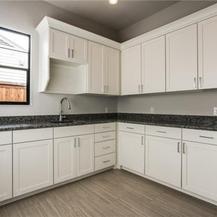 Inspiration för mellanstora klassiska l-formade grått tvättstugor enbart för tvätt, med en enkel diskho, skåp i shakerstil, vita skåp, granitbänkskiva, grått stänkskydd, grå väggar, klinkergolv i porslin, en tvättmaskin och torktumlare bredvid varandra och grått golv