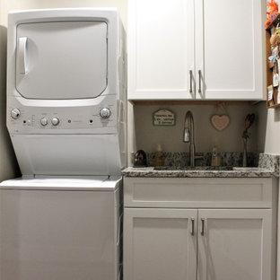 Idéer för att renovera ett litet vintage grå linjärt grått grovkök, med en enkel diskho, skåp i shakerstil, vita skåp, granitbänkskiva, grå väggar, mellanmörkt trägolv, en tvättpelare och brunt golv