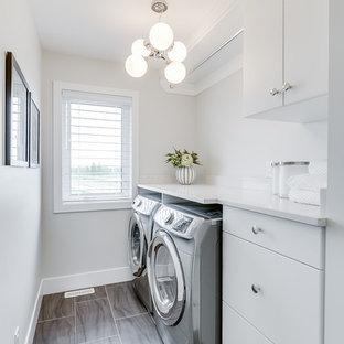 Idee per una sala lavanderia design di medie dimensioni con ante lisce, ante bianche, top in quarzite, pareti bianche e lavatrice e asciugatrice affiancate