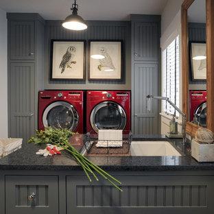Esempio di una grande lavanderia multiuso industriale con ante grigie, top in granito, pareti grigie, lavatrice e asciugatrice affiancate, ante in stile shaker e lavello sottopiano