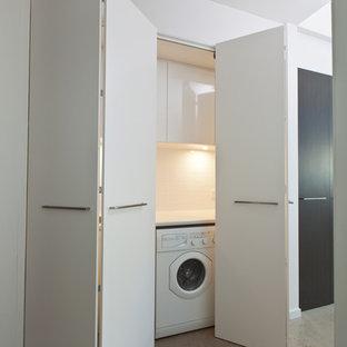 Modern inredning av en liten linjär tvättstuga enbart för tvätt, med släta luckor, vita skåp, laminatbänkskiva, vita väggar, betonggolv och en tvättmaskin och torktumlare bredvid varandra