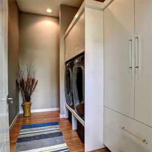 Foto di una piccola sala lavanderia design con ante lisce, ante bianche, pareti grigie, pavimento in bambù e lavatrice e asciugatrice affiancate