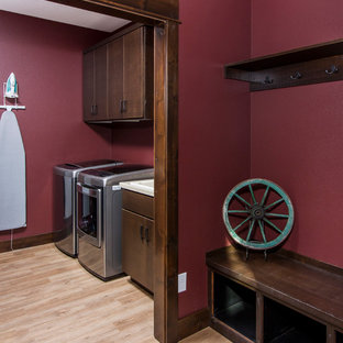 Inspiration for a country single-wall laundry room in Other with a drop-in sink, flat-panel cabinets, dark wood cabinets, red walls, light hardwood floors and a side-by-side washer and dryer.
