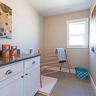 Exemple d'une buanderie parallèle chic dédiée et de taille moyenne avec un placard avec porte à panneau encastré, des portes de placard blanches, un plan de travail en quartz, un mur beige, un sol en carrelage de céramique et des machines côte à côte.