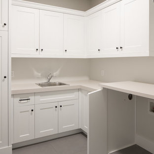 Photo of a large modern l-shaped separated utility room in Calgary with a single-bowl sink, shaker cabinets, white cabinets, laminate countertops, white walls, ceramic flooring, a side by side washer and dryer, grey floors and grey worktops.